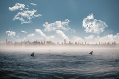Cityscape on horizon over shark infested sea Stock Photography