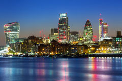 Cityscape of London with reflection in Thames river. At night, UK Stock Image