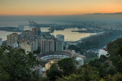 Cityscape Malaga with harbor by sunset and hills in background royalty free stock photos