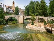 Cityscape med bron över floden på Alcala del Jucar, Castilla l Arkivbilder