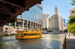 Cityscape med den Chicago vattentaxien bär passagerare längs Chicagoet River i dagen arkivfoto