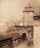 Cityscape of the medieval street with gates tower. Retro toned. Stock Photos