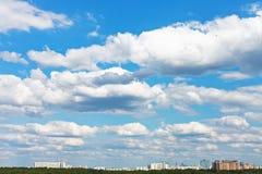 Cityscape met witte pluizige wolken in blauwe hemel Stock Afbeeldingen