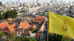 Cityscape of modern oriental town. View of houses roofs on streets of majestic Bangkok from Golden Mount Temple during. Sunset time. Yellow royal flag and stock video