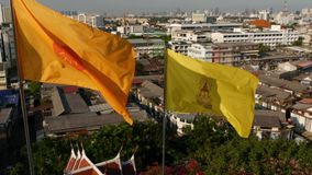 Cityscape of modern oriental town. View of houses roofs on streets of majestic Bangkok from Golden Mount Temple during. Sunset time. Yellow royal flag and stock footage