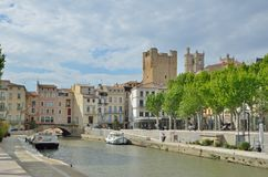 Cityscape of Narbonne. The canal de la Robine runs through the center of the French city Narbonne. There are the traditional townhouses and ancient towers behind Royalty Free Stock Images