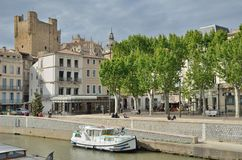 Cityscape of Narbonne. There are the traditional townhouses and ancient towers behind, the passerby and tourists, many shops and cafes along the embankment, two Royalty Free Stock Photos