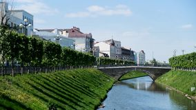 Cityscape with a narrow river surrounded by green foliage and white buildings. Stock footage. A picturesque street in a