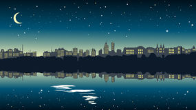 Cityscape at night near the lake. Royalty Free Stock Photography