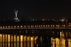 Cityscape på bakgrunden av en bro och en flod med en beautifully tänd staty arkivfoton