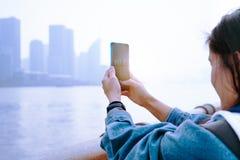 Cityscape på smartphonen Sikt till och med skärmen på den Shanghai staden på kvinnaskärmen, Kina royaltyfria foton