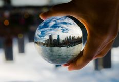 Cityscape photography in a clear glass crystal ball with dramatic clouds sky. stock photography
