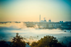 Cityscape of power plants and the field with fog Royalty Free Stock Image