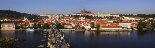 Cityscape of Prague with Castle and Charles Bridge. A lot of people walk on the Charles Bridge above Vltava river in Prague, Czech Republic Royalty Free Stock Images