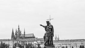 Cityscape of Prague in monochrome with statue of the Charles bridge in the foreground Royalty Free Stock Image