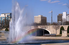 Cityscape with Rainbow in Water Fountain Stock Images