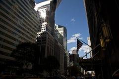 cityscape Ray ilumina a reflexão no arranha-céus e nas bandeiras dos EUA em t Imagem de Stock Royalty Free
