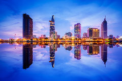 Cityscape in reflection of Ho Chi Minh city at beautiful twilight, viewed over Saigon river. Hochiminh city is the largest city in Vietnam with population Royalty Free Stock Photos