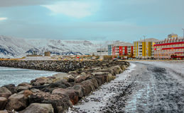 Cityscape in Reykjavik with red and yellow buildings. Reykjavik city view with stones and sea and bright decorated houses Royalty Free Stock Photo