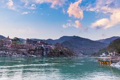 Cityscape of Rishikesh at sunset, holy town and travel destination in India. Colorful sky and clouds reflecting over the Ganges Ri Stock Photography