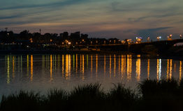 Cityscape with river after sunset. Irkutsk cityscape with Angara river after sunset with bridge and reflection of lights Stock Images