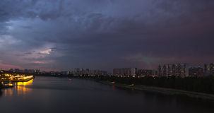 Cityscape with river traffic and movement of the clouds at dusk. Time lapse cityscape of tour boat traffic on river and the movement of the thunderstorm front at stock video