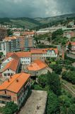 Cityscape with road and building amid trees. And mountainous landscape, in a cloudy day at Covilha. Known as the town of wool and snow, stands at Estrela ridge stock photo