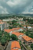 Cityscape with road and building amid trees. And mountainous landscape, in a cloudy day at Covilha. Known as the town of wool and snow, stands at Estrela ridge stock photography