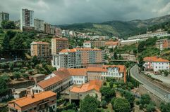 Cityscape with road and building amid trees. And mountainous landscape, in a cloudy day at Covilha. Known as the town of wool and snow, stands at Estrela ridge royalty free stock images