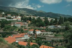 Cityscape with road and buildings amid trees. And mountainous landscape, in a cloudy day at Covilha. Known as the town of wool and snow, stands at Estrela ridge stock images