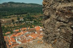 Cityscape with roofs seen by crenel in the castle wall. Cityscape with old house roofs and hilly landscape, seen by crenel in the castle wall at Castelo de Vide royalty free stock photography