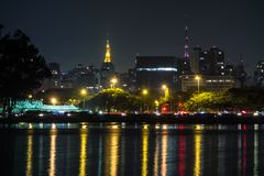 Sao paulo city, night, towers. Cityscape of sao paulo at night, from the lake of ibirapuera park, with two lit towers on back royalty free stock image