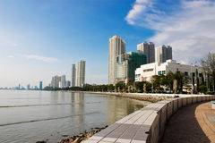 Cityscape by the seafront. Sea front view of modern building with blue white clouds sky Royalty Free Stock Photos
