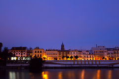 Cityscape of Seville by river in dusk Royalty Free Stock Images