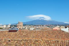 Cityscape of Sicilian Catania in Italy taken from the roof of a building in historical center. In the background there is famous. Mount Etna volcano overlooking royalty free stock image