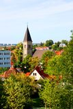 Cityscape of Stuttgart. A photo of Stuttgart in Germany with a old church and some houses among a park with green trees everywhere under a blue sunny sky Stock Photo