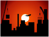 Cityscape at sunset. With cranes in background Royalty Free Stock Image