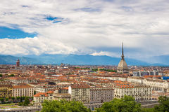Cityscape of Torino Turin, Italy with the Mole Antonelliana towering over the buildings. Wind storm clouds over the Alps in the Royalty Free Stock Photography
