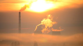 Cityscape urban landscape factory and large pipes smoke at sunrise sun shining. Bright cityscape bright urban landscape with a factory and large pipes with smoke stock video footage
