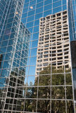 Cityscape: Urban Reflections in Highrise Glass. Reflections of trees and office buildings in the mirror glass wall of a futuristic looking high rise corporate Royalty Free Stock Photos