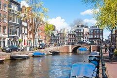 Cityscape van Amsterdam met rij van auto's, fietsen en boten langs het kanaal van Amsterdam tijdens de zonnige dag op 30,2015 wor Stock Afbeelding