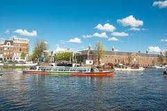 Cityscape van Amsterdam, toeristen geniet kanaal van cruise, Magere Brug (Magere Brug), is de Kluis Amsterdam zichtbaar op de ach Stock Fotografie