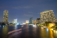 Cityscape van Bangkok met rivier en boot bij nacht Stock Foto
