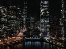 Cityscape van Chicago met nachtlichten wordt verlicht die weg van de Rivier die van Chicago nadenken Stock Afbeeldingen