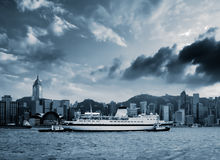 Cityscape of Victoria harbor with boat in HK Stock Images
