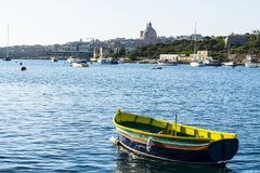 Cityscape view with Basilica. Of Our Lady of Mount Carmel on the island of Malta. Yachts docked at the port of Valletta. A shabby old boat among the luxury Stock Photography