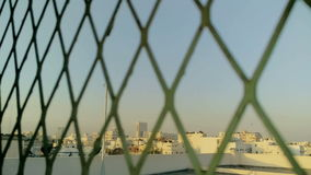 Cityscape view from behind the iron net stock footage