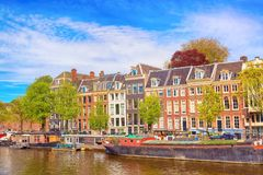 Cityscape view of the canal of Amsterdam in summer with a blue sky, house boats and traditional old houses. Picturesque of Amsterd. Am, North Holland, The stock image