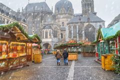 Cityscape - view of the Christmas Market with passing pair on the background the Aachen Cathedral. North Rhine-Westphalia, Germany stock photo