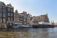 Cityscape view from river Amstel with brick houses facades and containers on barges with graffiti. Amsterdam, The Netherlands, October 10, 2018: Cityscape view royalty free stock photos
